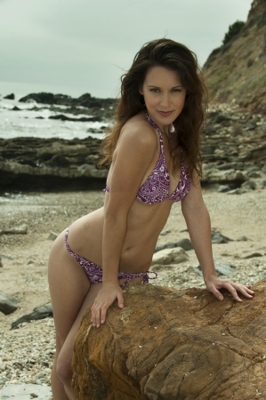 Relaxed attractive brunette girl wearing purple bikini poses on the rock by the sea  Evening soft light at coastline of Rancho Palos Verdes, CA   photo