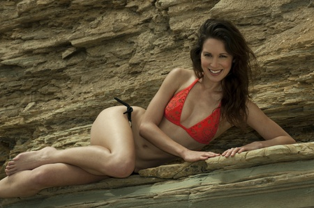 brune: Attractive brune girl posing sexy at the rocks at Palos Verdes secret cove beach, CA Stock Photo