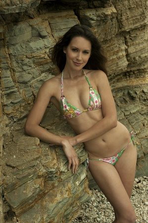 Attractive brunette girl posing sexy in brazilian bikini in front of rocks at Palos Verdes secret cove beach, CA photo