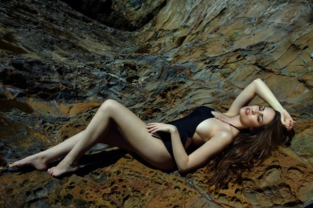 Swimsuit model posing sexy in front of black lava field on at Palos Verdes, CA  photo