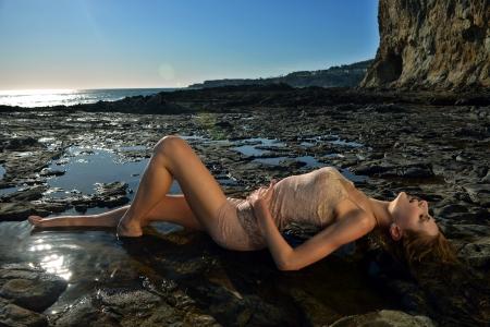 Swimsuit model posing sexy in de voorkant van zwarte lava veld op in Palos Verdes, CA Stockfoto