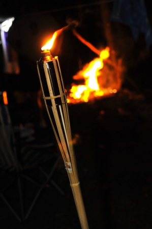 Camp fire and flame of a bamboo torch burning in the night