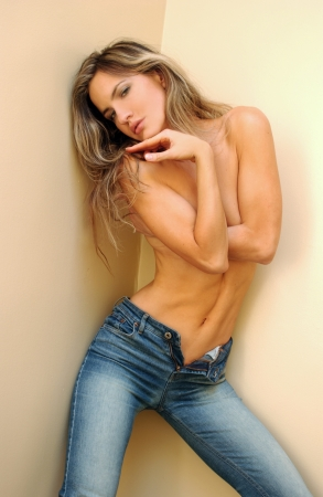 Fashion photo of young sensual woman in jeans over wall background  Stock Photo