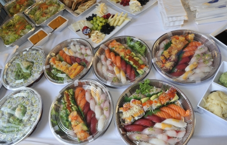 Sushi, sashimi, rolls on trays and cold snacks being prepared for a party on buffet table, catering  Imagens