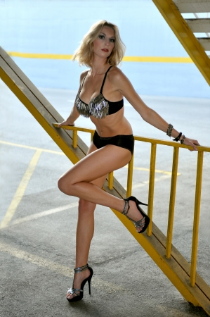 Tall blond woman posing very sexy in bikini in a parking lot garage exterior.