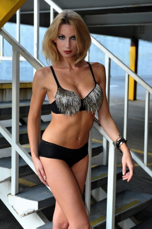 Tall blond woman posing very sexy in bikini in a parking lot garage exterior. photo