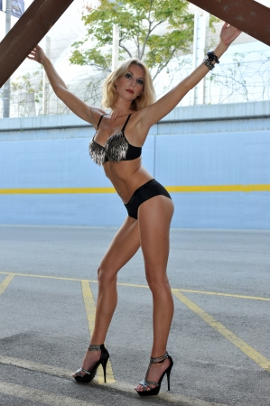 Tall blond woman posing very sexy in bikini in a parking lot garage exterior. Stock Photo - 19159608