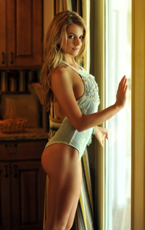 Glamor blond girl posing pretty at old fashioned house interior wearing designers lingerie and custom jewelery photo