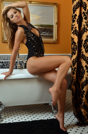 luxury hotel room: Fashion model posing pretty at the bathroom interiors wearing designers one piece swimsuit and custom jewelery Stock Photo