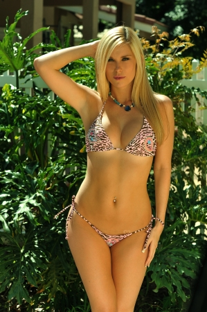 Pretty blond girl wearing bikini looking straight to the camera in tropical garden