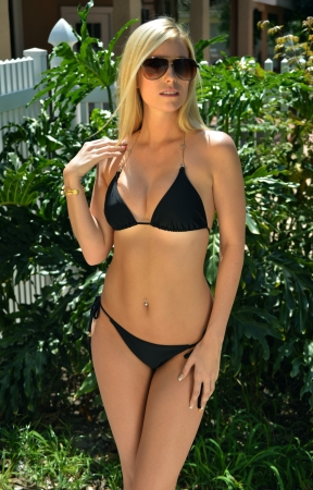Pretty blond girl wearing bikini looking straight to the camera in tropical garden photo