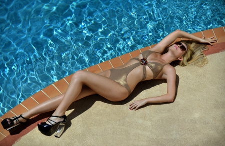 Beautiful blond girl taking sunbath at the edge of swimming pool Stock Photo