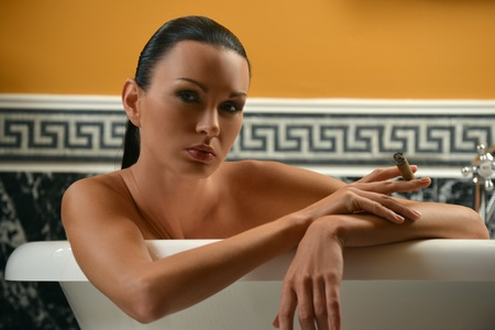 luxury hotel room: Portrait of sophisticated brunette woman in the bath holding cigar Stock Photo