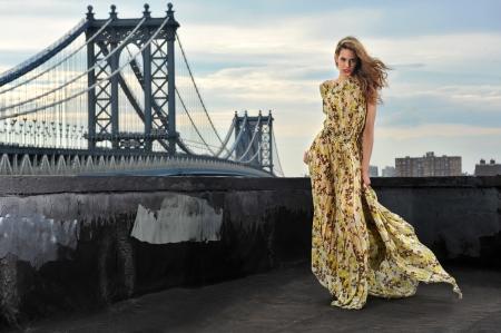 traje de gala: Modelo de moda sexy, con un vestido de noche largo de la ubicaci�n en la azotea con la construcci�n de puentes de metal en el fondo