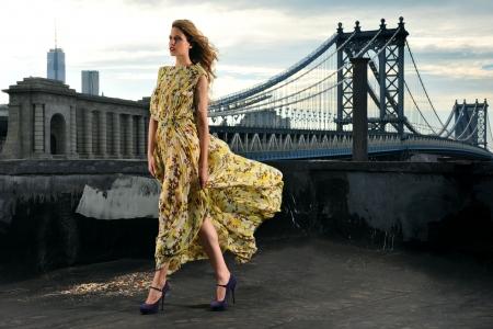 robe de soir�e: Mannequin posant sexy, v�tu de la robe de soir�e longue sur l'emplacement sur le toit avec la construction du pont m�tallique sur le fond