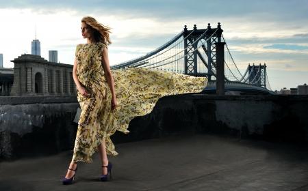 セクシー、身に着けている長いイブニング ドレス屋上上金属橋建設の背景にポーズをとってファッション モデル 写真素材