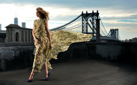 Fashion model posing sexy, wearing long evening dress on rooftop location with metal bridge construction on background Archivio Fotografico
