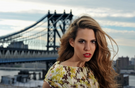 Close up portrait of fashion model with full sexy hair and red lips posing on rooftop location with metal bridge construction on background photo
