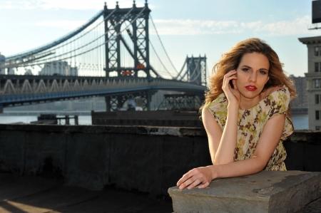 traje de gala: Retrato de modelo de moda posando sexy, con un vestido de noche largo de la ubicación en la azotea con la construcción del puente de metal en el fondo