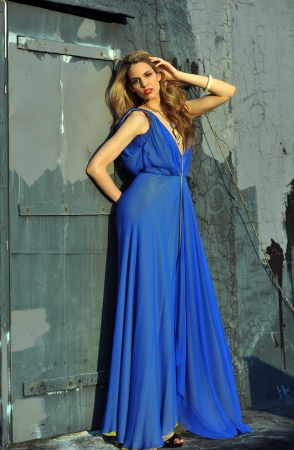 Fashion model posing sexy, wearing long blue evening dress on rooftop location  Stock Photo - 20454225