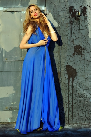 Fashion model posing sexy, wearing long blue evening dress on rooftop location  Stock Photo - 20454233