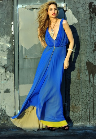 Fashion model posing sexy, wearing long blue evening dress on rooftop location  Stock Photo