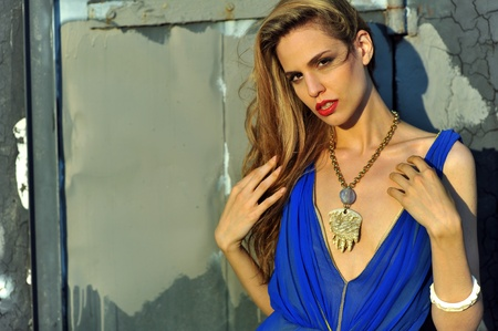 Closeup portrair of fashion model with full hair and red lips,  posing sexy and wearing long blue evening dress and fashion acessories
