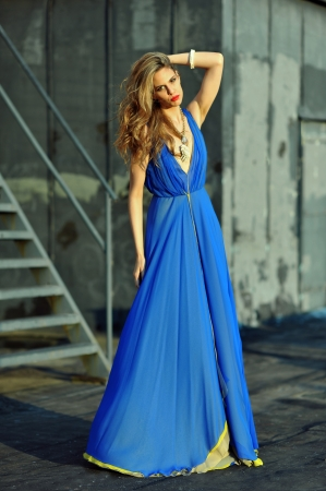 Fashion model posing sexy, wearing long blue evening dress on rooftop location Stock Photo - 20454154