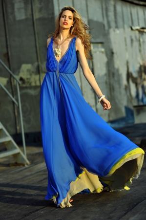 Fashion model posing sexy, wearing long blue evening dress on rooftop location  Stock Photo - 20454177