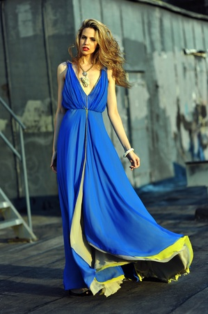 Fashion model posing sexy, wearing long blue evening dress on rooftop location  版權商用圖片