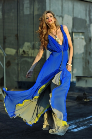 fashion: Fashion model posing sexy, wearing long blue evening dress on rooftop location  Stock Photo