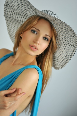 Portrait of young sexy blond girl wearing summer hat and blue dress photo