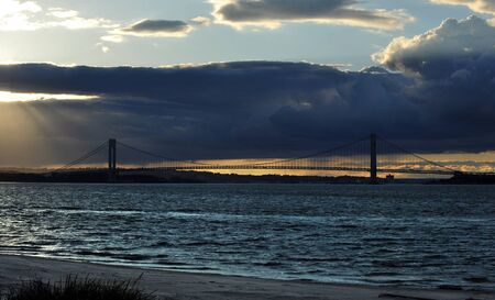 Sunbeams coming through the clouds at sunset time on hudson river with Verrazano bridge on background photo