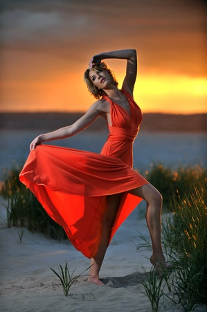 Young fashion model posing in red dress on sunset time with effective background of clouds and Verrazano bridge photo