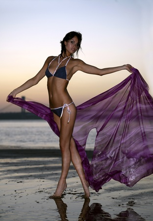 Beautiful fashion model in design bikini holding floating bright fabric standing on the beach during  sunset time with effective background of sky photo