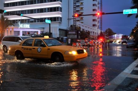 マイアミビーチ、フロリダ州 - 7 月 18 日: 車重マイアミビーチ、フロリダ州のフロリダ州で 2013 年 7 月 18 日の雨の後の通りは水浸しやマイアミ サウ 報道画像