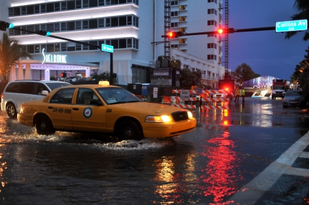 miami south beach: MIAMI BEACH, FL - JULY 18: Cars moving on flooded streets and roads of Miami South Beach  after heavy rains in Florida July 18, 2013 in Miami Beach, Florida