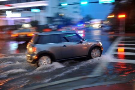 MIAMI BEACH, FL - 18 juli: Auto's bewegen op ondergelopen straten en wegen van Miami South Beach na zware regenval in Florida 18 juli 2013 in Miami Beach, Florida