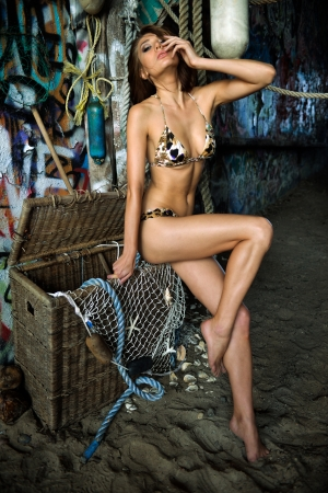 Swimsuit model posing sexy in front of graffiti background with marine style accessories hanging on the wall made of drift wood photo