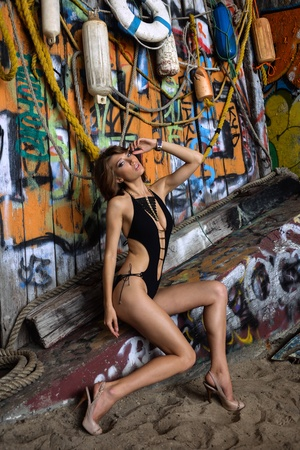 Gorgeous swimsuit model wearing onepiece swimsuit and jewelry  posing sexy in front of graffiti background with marine style accessories  photo
