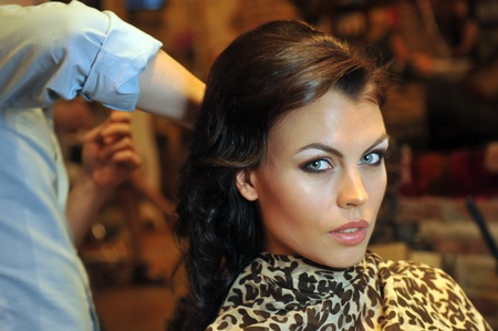 Warm light beauty shoot of brunette model in Beauty salon interior during hairstyling process