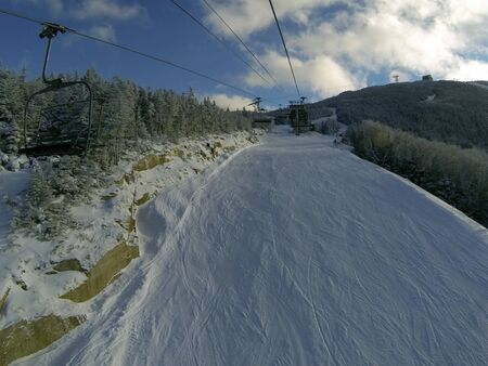 Winter mountains panorama with ski slopes and ski lifts at sunny day photo