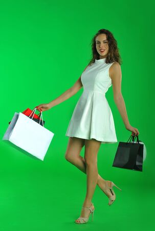 removable: portrait of a young sexy woman with shopping bags posing against a removable green chroma key background