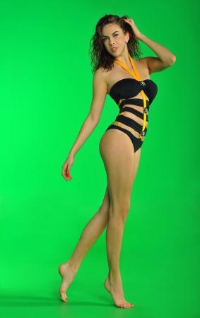 portret van een jonge sexy vrouw dragen ontwerpers zwembroek en poseren tegen een verwijderbare chroma key achtergrond