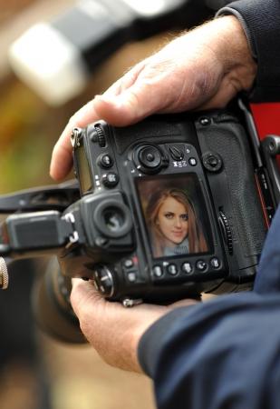 DSLR camera in de hand tonen screen preview met model portret