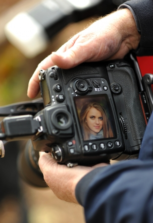 DSLR camera in hand showing screen preview with model portrait
