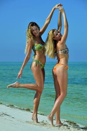 Dos modelos en bikini posando sexy en la ubicaci�n tropical playa photo