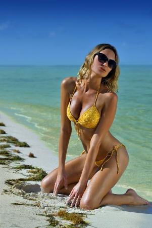 Bikini model poseert sexy in de voorkant van de camera bij tropisch strand locatie Stockfoto