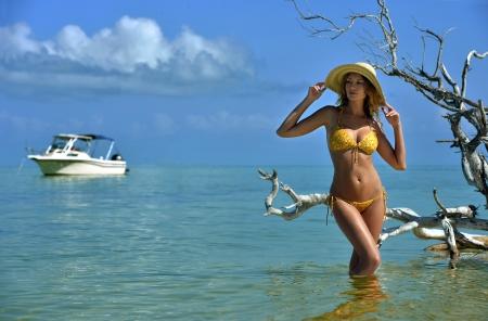 Bikini-Modell in Stroh Hut posiert sexy vor der Kamera am tropischen Strand Lage mit Treibholz Baum und Fischerboot Standard-Bild - 24816315