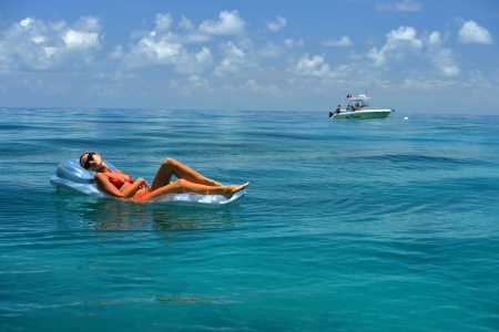 Woman in red bikini on floating device at open waters of carribbean photo